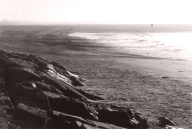 Man in distance, as fog burns off on beach